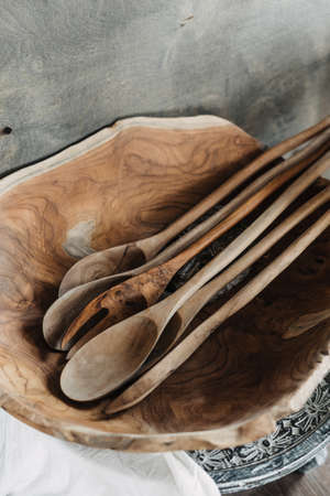 Close up view at handmade carved spoons in wooden bowl on cozy kitchen. Concept natural materials. Selective focus on home decor Standard-Bild