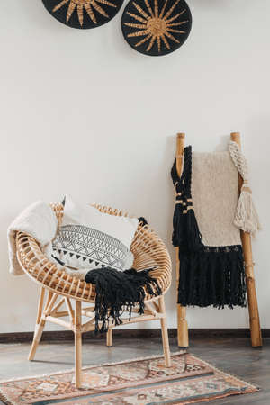 Vertical view of cushions and plaid on rattan chair near bamboo ladder in ethnic interior design. Concept of home decor, natural material furniture, wicker armchair in hygge living room