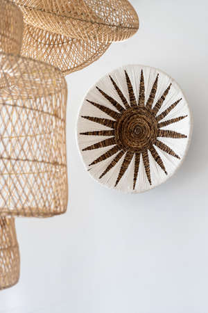 Vertical view of home decor with natural materials hanging on white copy space wall at room with bohemian style, near handmade wicker lampshade Standard-Bild