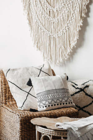 Vertical view of cozy living room interior in bali or indonesian style, with home decor, wicker furniture, armchair with cushions and macrame on white wall