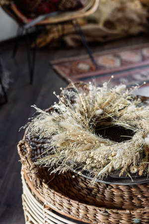 Vertical view of beautiful braided wreath of natural dried flowers lying at wooden plate on coffee table against blurred living room in bohemian style on background