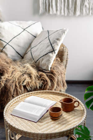 Concept of recreation, relaxation. Weekend at cozy house. Wicker coffee table with open book and wooden cup with beverage standing near rattan armchair. Living room interior at boho chic style