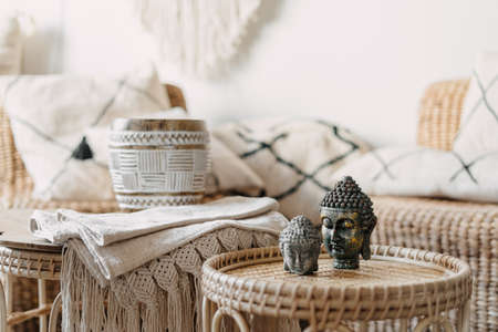 Selective focus at two Buddha statue standing on bamboo coffee table in bright living room interior at bohemian style. Concept mental health and recreation. House with natural materials furniture