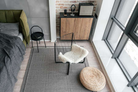 View above on relax area with metal chair and straw ottoman near panoramic window and commode with with stereo speaker nearby of headphones and smartphone in stylish suite room in hotel