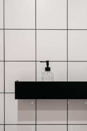 Closeup at bathroom shelf, modern shower cabin. Clean bath with soap, shampoo, beauty product in bottle. Shower lotion liquid in transparent case. Treatment product at white wall.