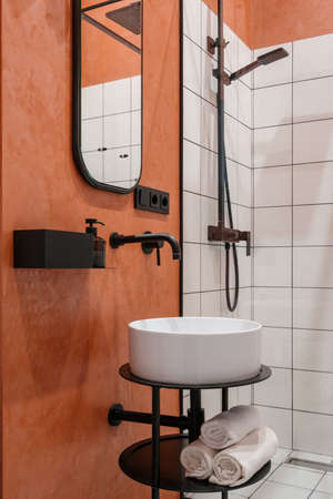 Bathroom interior at modern home, closeup at furniture. Apartment design for clean indoor room, contemporary style with ceramic faucet. Vertical shot of modern bath with white tile.