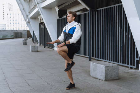 Healthy lifestyle and everyday sport concept. Side view of athlete jumping up, doing breathing exercise in cardio training. Sporty man workout outdoor in city