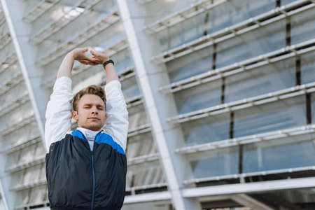 Calm man in good sporty shape stretching upper body on daily training. Sportsman warming up before running, raised hands, standing with closed eyes outdoor in city