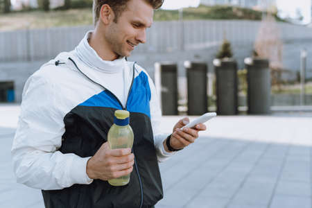 Side profile view of smiling sportsman holding bottle with water in hand, using online app in modern smartphone, tracking heart rate, running speed and personal best on daily workout Standard-Bild