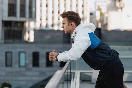 Side profile view of calm sportsman resting after everyday sport training in city. Man in sportswear looking at street view, leaning against the handrail. Healthy lifestyle and recreation concept