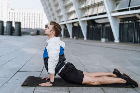 Healthcare and healthy lifestyle concept. Profile view of calm man in cobra asana doing yoga training, strengthen the spine, doing back bend warming up outdoor, before running in city