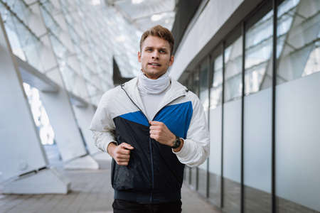 Healthy lifestyle concept. Young man running in the city. Athlete in sportswear warming up before every day workout. Healthy athlete or football player doing cardio exercise outdoors