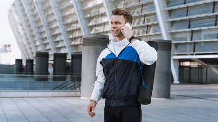Side view of confident man with yoga mat behind his back talking at modern smartphone before sport training in city. Sportsman prepare to daily workout, standing outdoor Standard-Bild