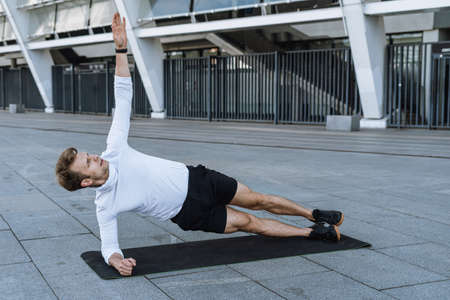 Workout concept. Athlete standing in side plank on yoga mat, raised hand up, looking at arm. Full length portrait of sporty man doing exercise on core and balance, training outdoor in city