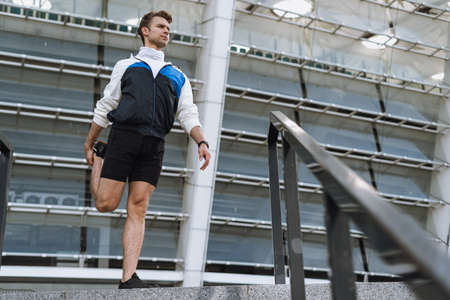 Healthy lifestyle concept. Low angle view of sportsman warming up his body, stretching legs before weekend run in city. Man standing outdoors, looking a side, pull up leg Standard-Bild