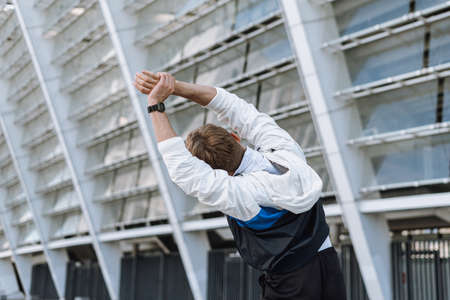 Back view of young sportsman raised hands up, stretching his body before morning run in city. Man warming up standing against urban background
