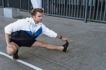 Full length portrait of sporty man stretching legs, training outdoor in city. Athlete warming up before daily run on urban street. Concept of healthy lifestyle and physical activity Standard-Bild