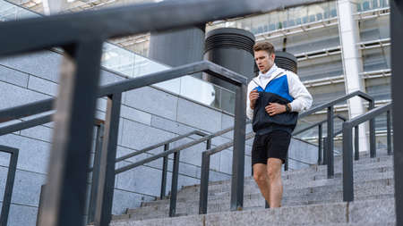 Low angle side view of runner doing sport training outdoor in city. Man running down the steps, making his daily cardio and warming up exercise. Physical activity concept