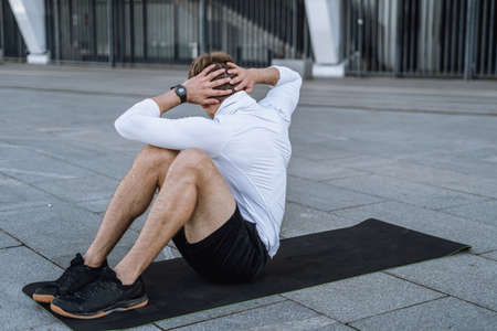 Man doing abs exercise on yoga mat. Back rear view of sportsman in sportswear training outdoor in city, turning aside and making body stronger with daily workout