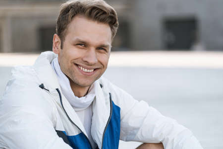 Concept of sportive and healthy lifestyle. Close up portrait happy sportsman looking at camera and smiling wide, sitting outdoor against blurred copy space city background