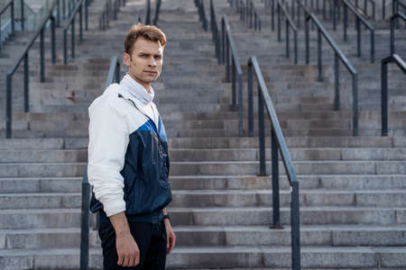 Side view of confident sportsman standing against steps, looking at camera with serious face. Man in sportswear preparing to daily outdoors training. Background with stairs on urban street, copy space