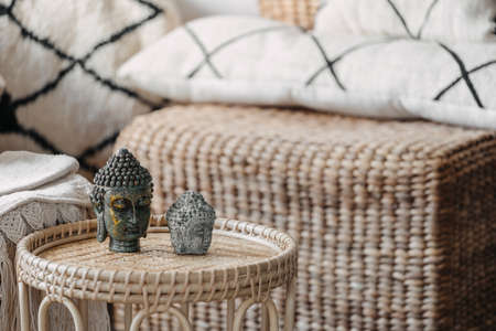 Close up view of Buddha head standing on wicked coffee table. Home decor on bamboo furniture with natural materials in bright living room interior at bohemian style. Calmness and mental health concept