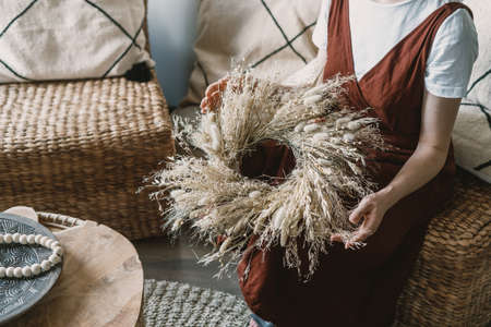 Cropped woman holding handmade braided wreath of dried plants in boho chic style, sitting on wicker armchair in florist studio. Female working at flower shop with eco materials