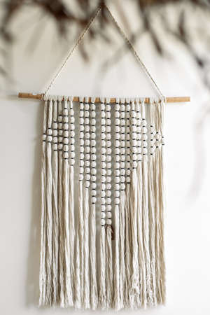 Vertical view of white handmade macrame hanging on wall in cozy living room. Home decor in bedroom with bohemian style or ethnic interior design