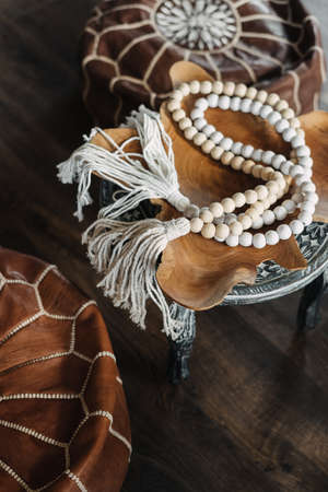High angle and vertical view of white wooden rosary beads on pouf with ethnic ornament. Home decor at bohemian style with natural materials