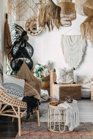 Vertical view of cozy coffee shop or living room with ethnic interior design. Concept of bohemian style at house with unique home decor, rattan furniture, cushions, armchair, bamboo coffee table