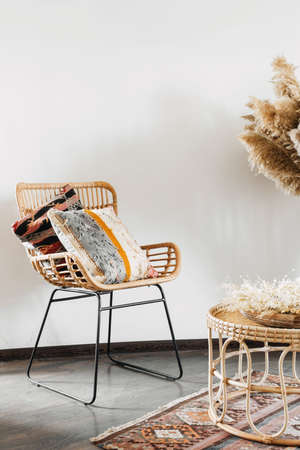 Vertical view of rattan or bamboo wicker chair standing in living room interior at bohemian style. Bedroom with armchair and ethnic ornamental cushions. Concept of furniture with natural materials
