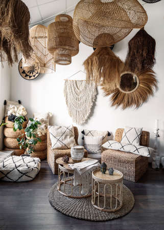 Ethnic living room interior with home decor and furniture in boho style. Vertical view of cozy apartment with cushions on rattan armchair, bamboo coffee table and hanging ceiling lamps Standard-Bild
