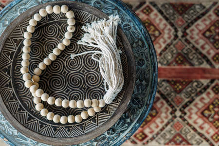 Flat lay view of white rosary beads on carved wooden plate, against ethnic colorful carpet on blurred copy space background. Top view of home decor at bohemian style with natural materials Standard-Bild