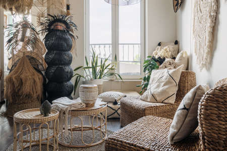 Rattan armchair with cushions near bamboo coffee table in bright living room with boho interior design. Concept of home decor and comfortable furniture in showroom
