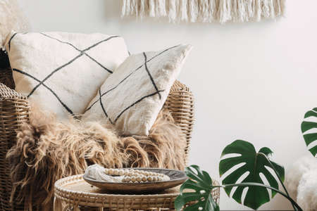 Close up view on comfortable armchair with cushions near coffee table. Room with ethnic interior, boho home decor and natural material furniture Standard-Bild