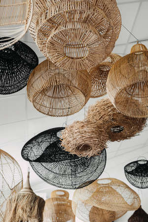 Low angle view of many handmade and wicker lampshade with natural materials hanging in showroom. Vertical view of lighting equipment in boho chic style