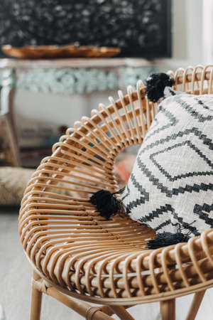 Close up view of rattan armchair with cushions in bohemian style living room. Concept of bamboo furniture and other home decor in bright house with ethnic interior design Standard-Bild
