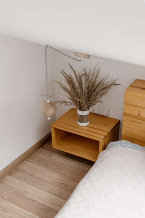 Vertical and high angle view of wooden nightstand with home decor near comfortable bed in light bedroom. Concept of cozy room in contemporary apartment