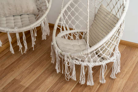 Two comfortable hanging rope swings with soft cushions over wooden laminate or hardwood parquet floor. Modern bedroom or living room interior with copy space. Recreation, relaxation concept