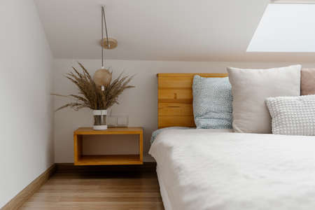 Modern apartment with vase on wood nightstand near comfortable bed in cozy bedroom. Home decor and wooden furniture in white minimalist room Standard-Bild