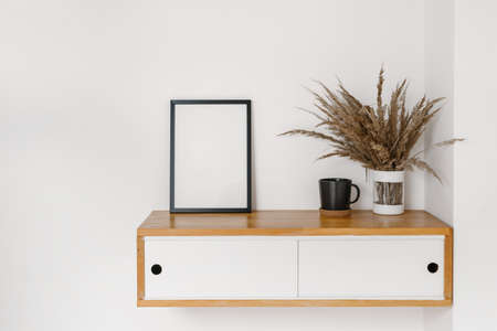 Concept of home decor in living room or bedroom. Mockup picture frame, cup and dry plants in vase at wooden hanging shelf with drawers. Furniture against white copy space wall Standard-Bild