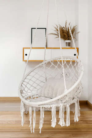 Concept of living room or bedroom furnishing. Vertical view of hanging rope swing with cushion against mockup picture frame, cup and dry plants in vase at wooden shelf with drawers Standard-Bild