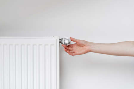 Cropped view of woman hand adjusting thermostat on white heating radiator. Consumption of natural resource, saving energy and warm home concept