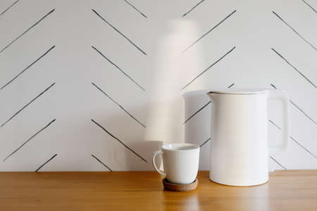 White and modern electric teapot and cup for coffee or herbal tea on wooden table against white copy space wall. Concept of cozy kitchen and morning beverage