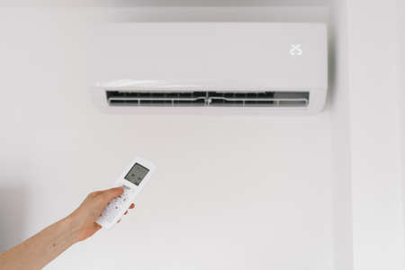 Cropped view of woman hand holding remote controller against air conditioner, choose air purification mode or comfort temperature in office. Concept of modern appliance for climate control at home