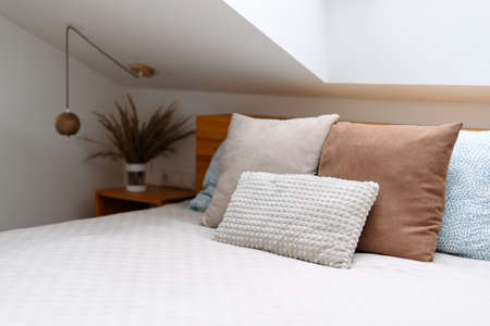 Healthy sleep, recreation, relaxation concept. Selective focus on orthopedic mattress with memory foam. Cozy room with cushions on bed in bedroom against wooden furniture on blurred background
