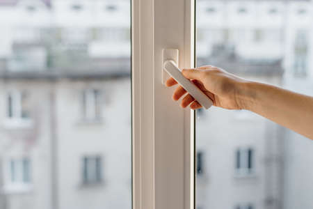 Cropped view of woman hand open pvc window with double glazing. Concept of noise cancellation and airing the room