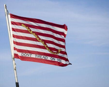 The US Navy Jack flag flying against a blue sky.