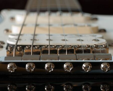 A macro view of a electric guitar bridge.