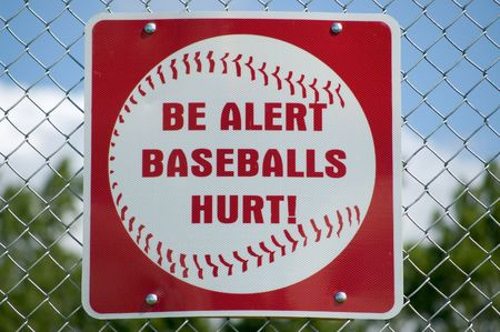 backstop: A sign posted on the backstop of a baseball field making people aware of flying baseballs.